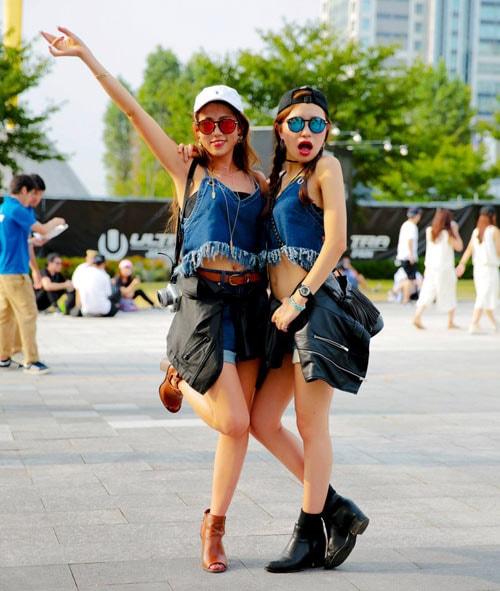 デニムのキャミソールでへそ出しファッションを楽しむ女性